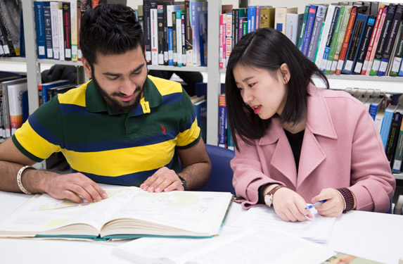 Two Students sharing one book inside the library