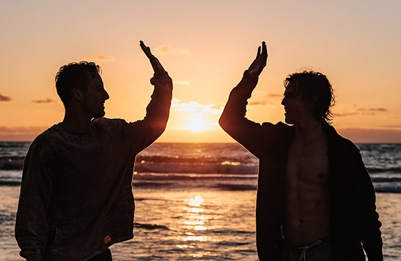 Two students high fiving at the beach