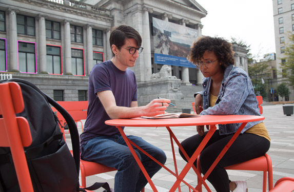 Two students studying together outside the campus