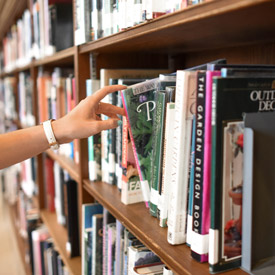 Choosing a book inside the library at Alexander College