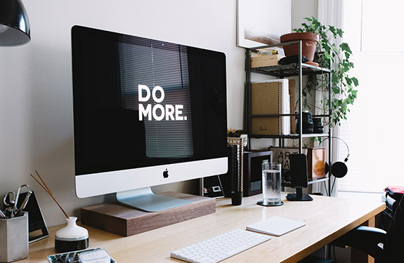 Work desk with a 'Do More' screensaver on computer