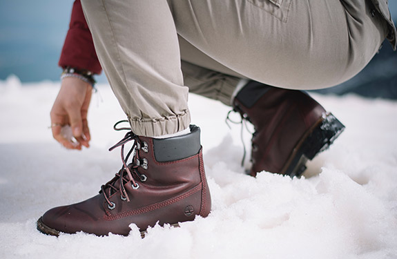 Person wearing Timberland boots in snow crouched down