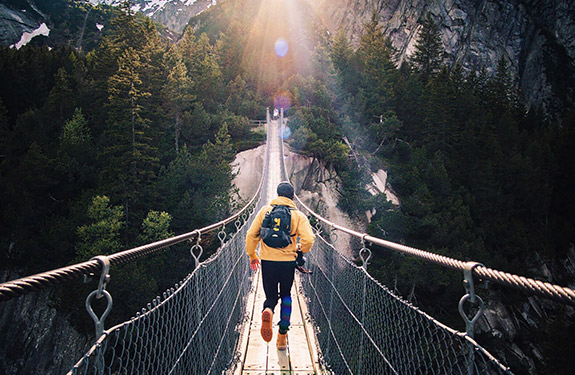 Person hiking as he crosses a suspension bridge
