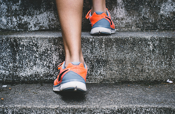 Female student walking up stairs for exercise