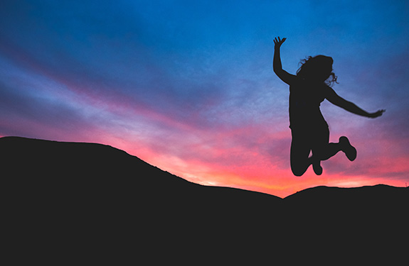 Jumping girl silhouette in front of sunset