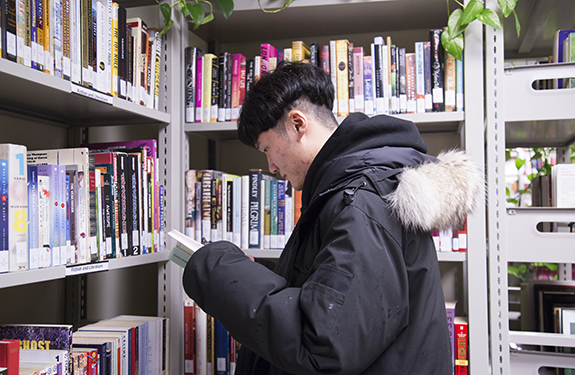Chinese Student at Alexander College Reading Book Inside The Library