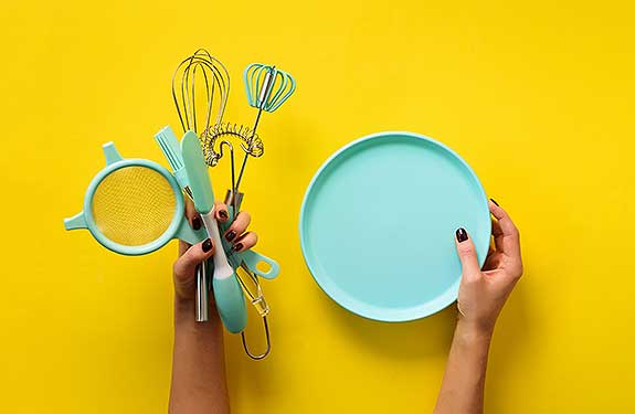 girl holding kitchen utensils for baking