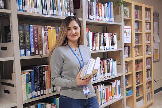 Student Worker Posing for the Camera while holding a book