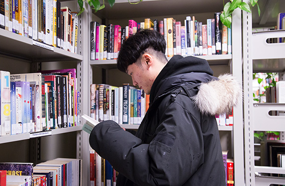 student reading a book inside the library