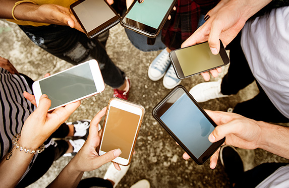 Young adults using smartphones in a circle social media
