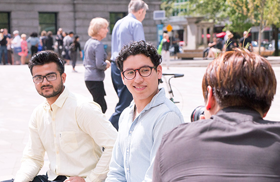 international students smiling at the camera behind the scenes
