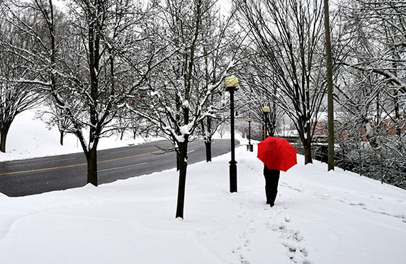Woman with a red umbrella walking in snow in the city next to a street